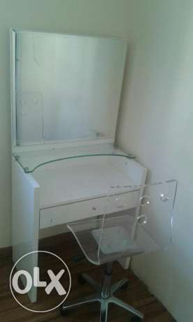 A dressing table with a mirror & a chair