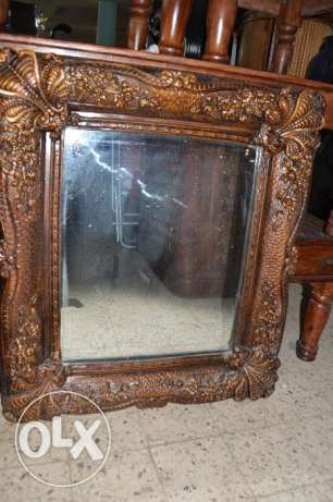 a mirror with solid wood cader