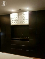 A bedroom closet with a tv unit