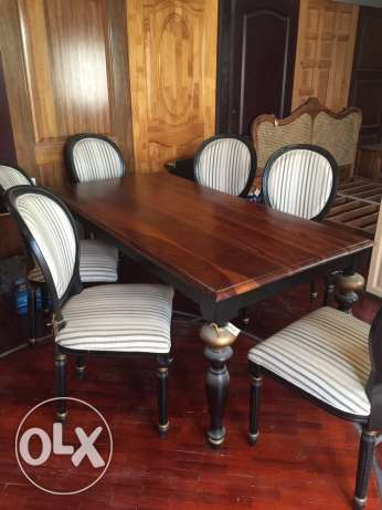 a solid wood dining table with 6 chairs