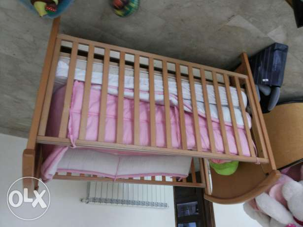 Wooden Baby bed with cushions and tires to turn the bed to swinger