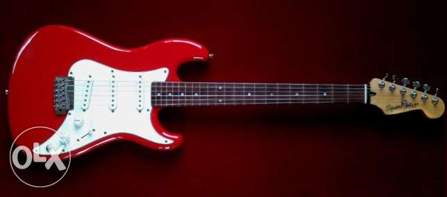 red squier electric guitar with amplifier and stand