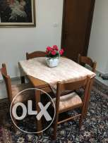 Dinning or kitchen table with four wooden chairs.