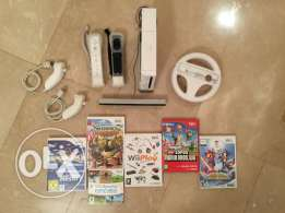 NINTENDO WII with 5 games, 2 controllers, and racing wheel