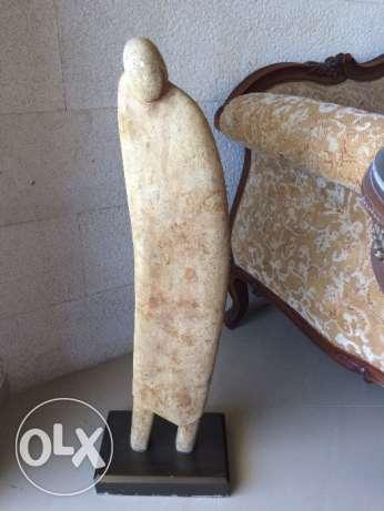 Limestone statue of an abstract person with a rectangular base.